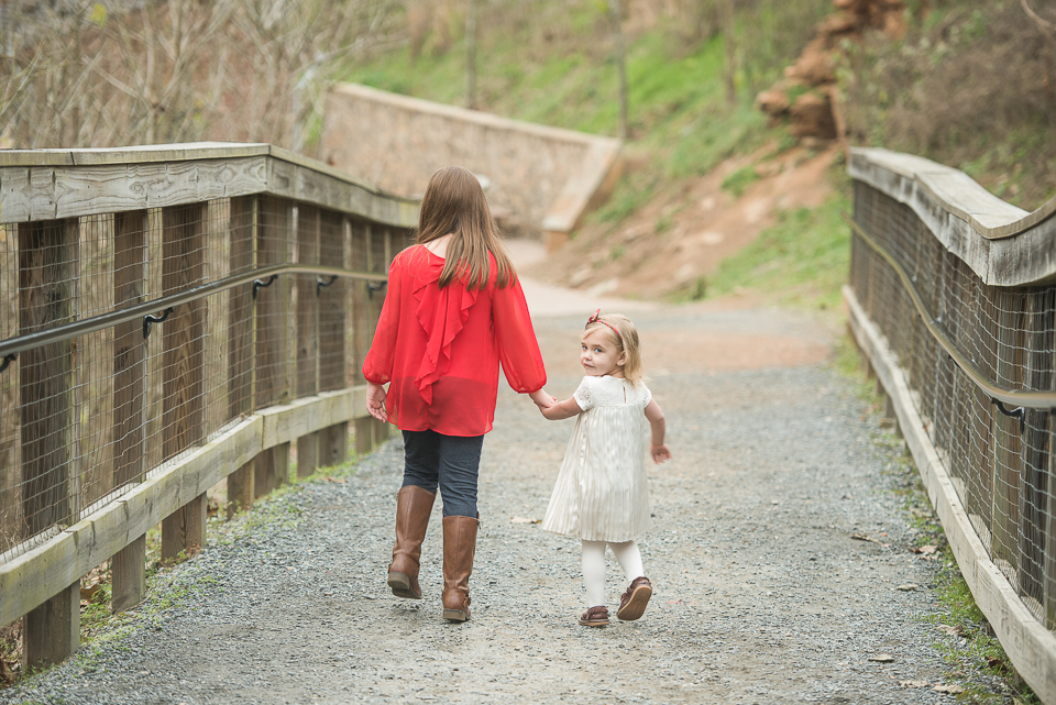 big sister and little sister holding hands walking on bridge