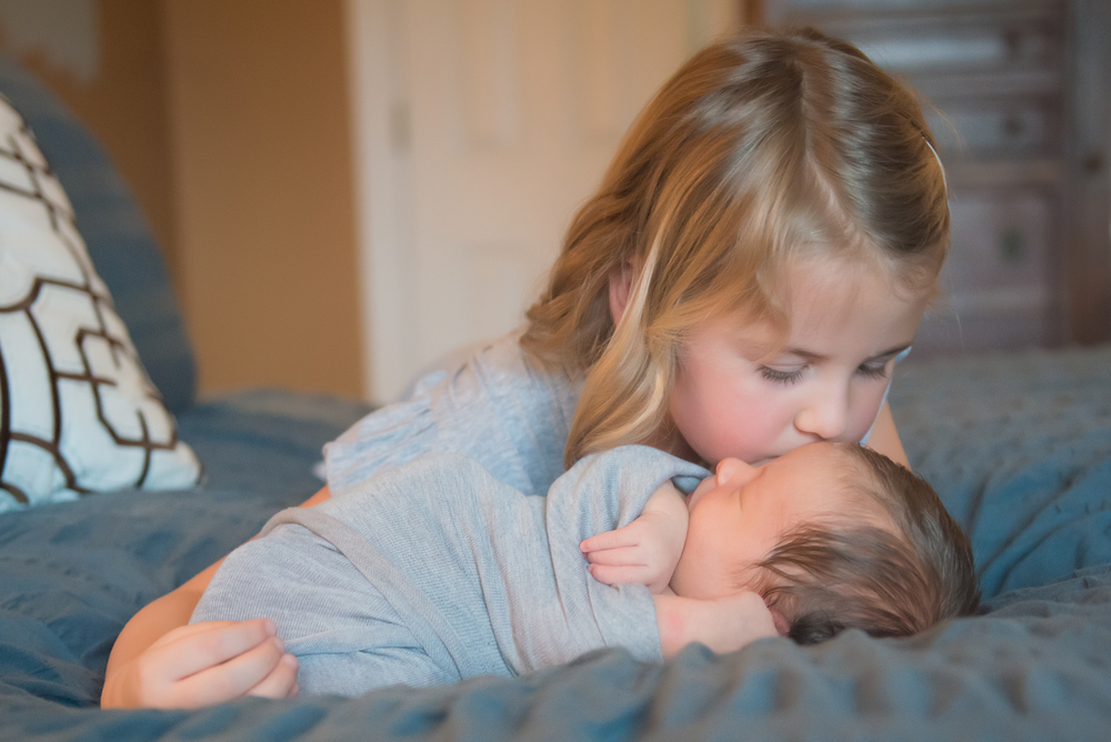 sister kissing newborn brother