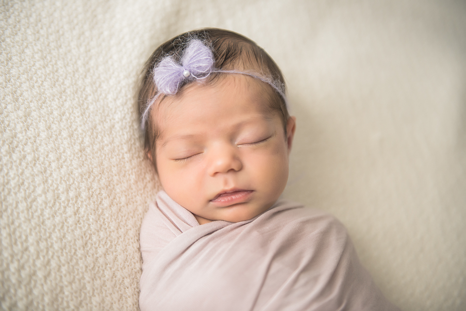 beautiful newborn girl in purple bow