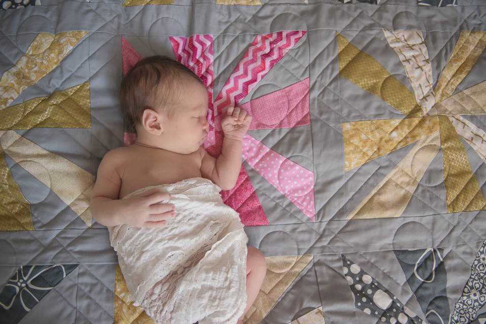 newborn sleeping on quilt