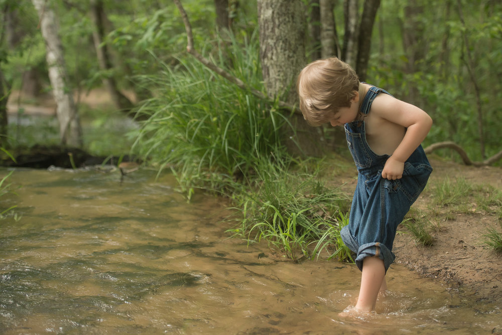 3 year old boy playing in the creek
