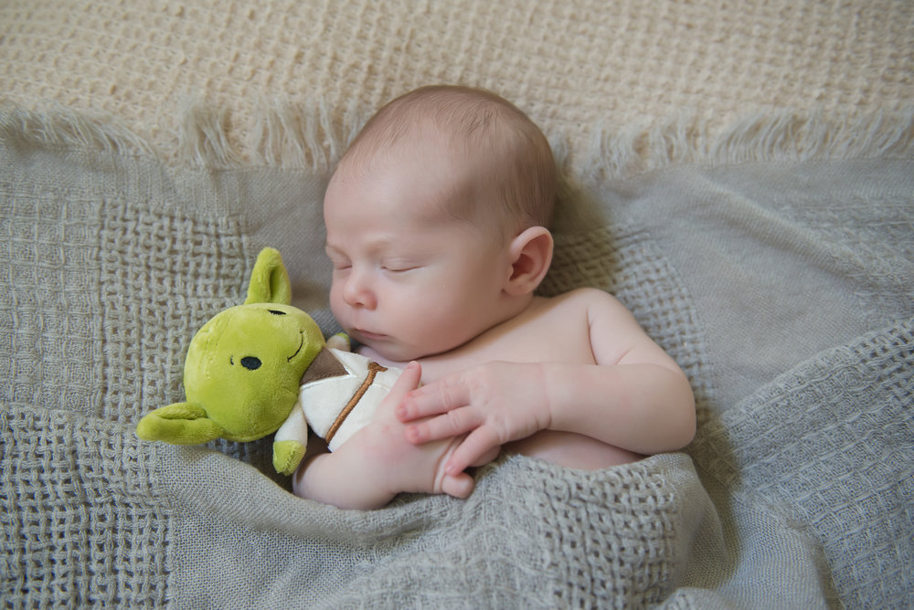 newborn boy snuggling yoda