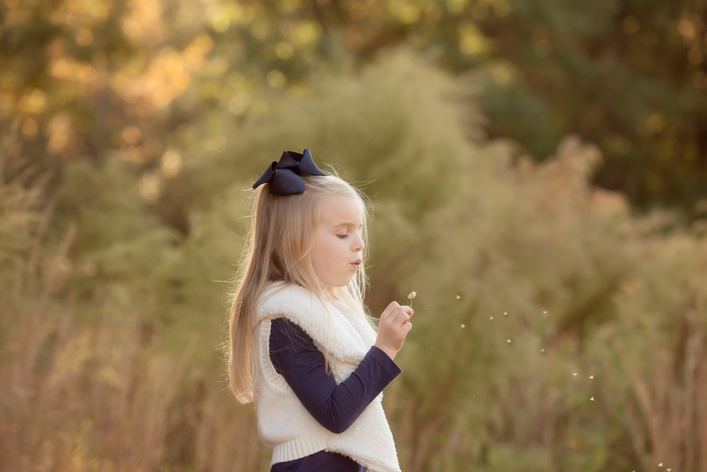 5 year old girl blowing dandelions