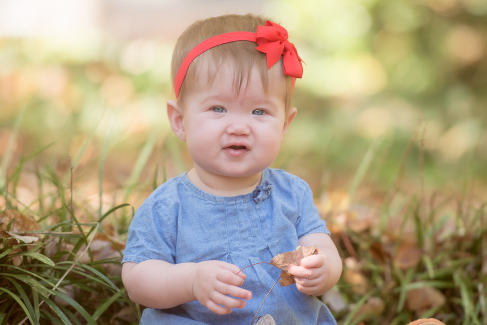 baby girl in red bow leaves