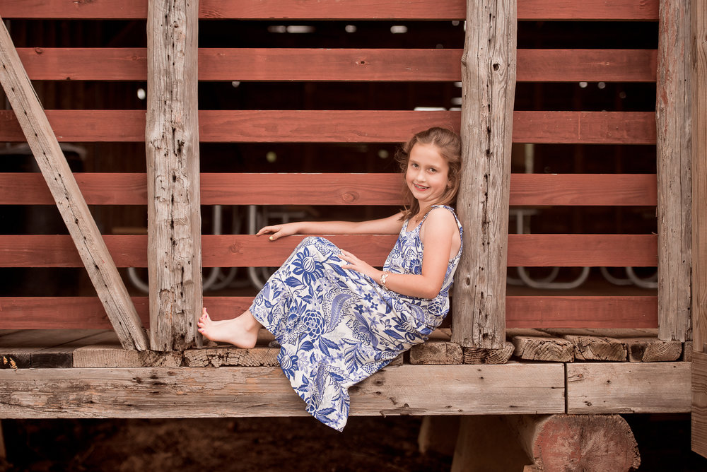 young girl sitting on side of barn