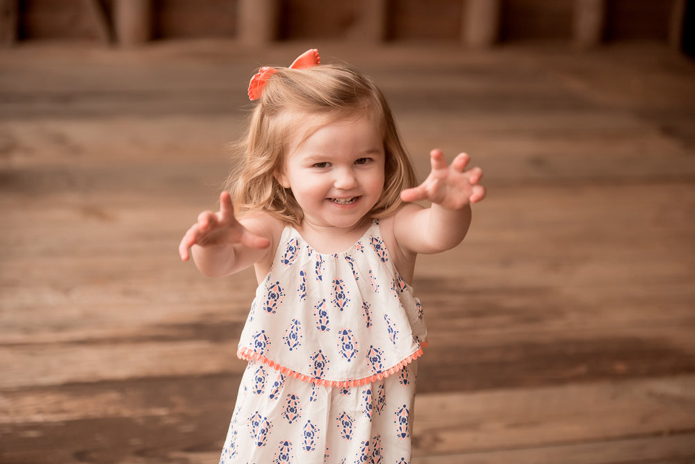 toddler girl smiling and reaching up