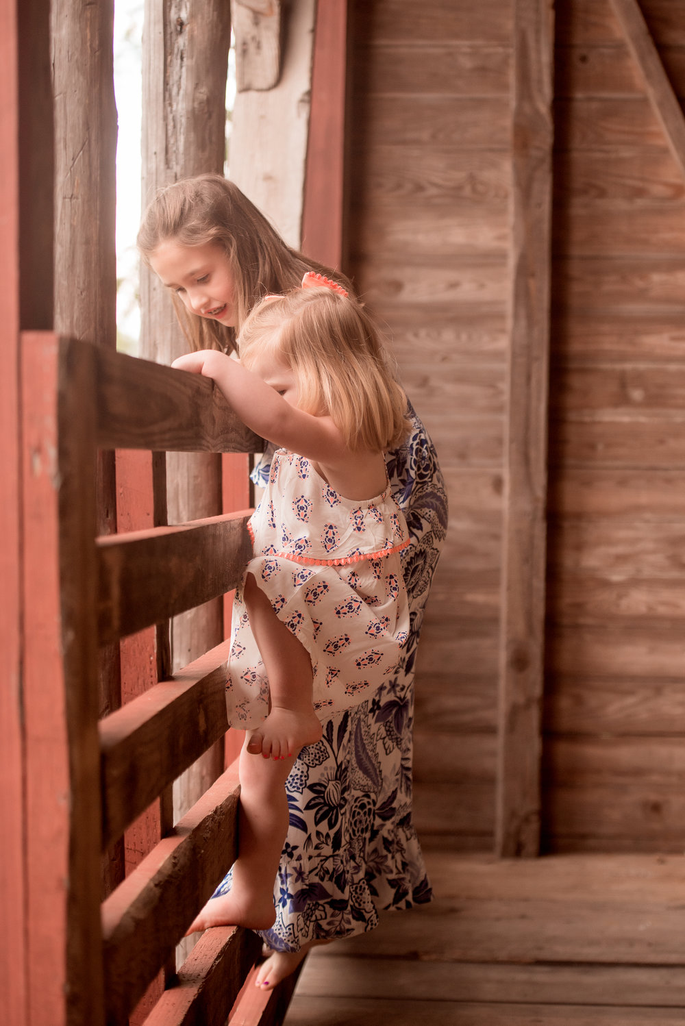 sisters climbing on barn rail