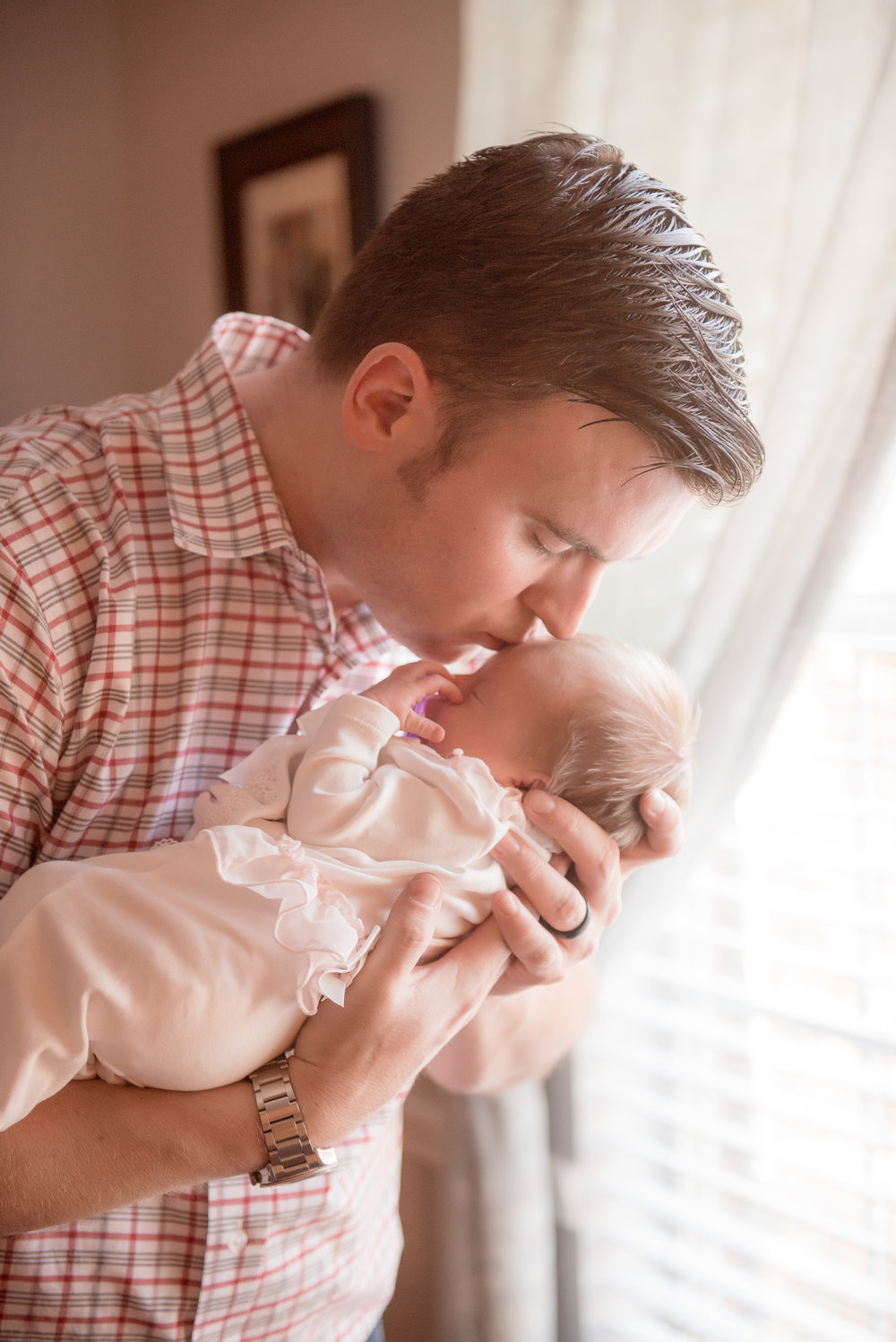 dad kissing newborn daughter