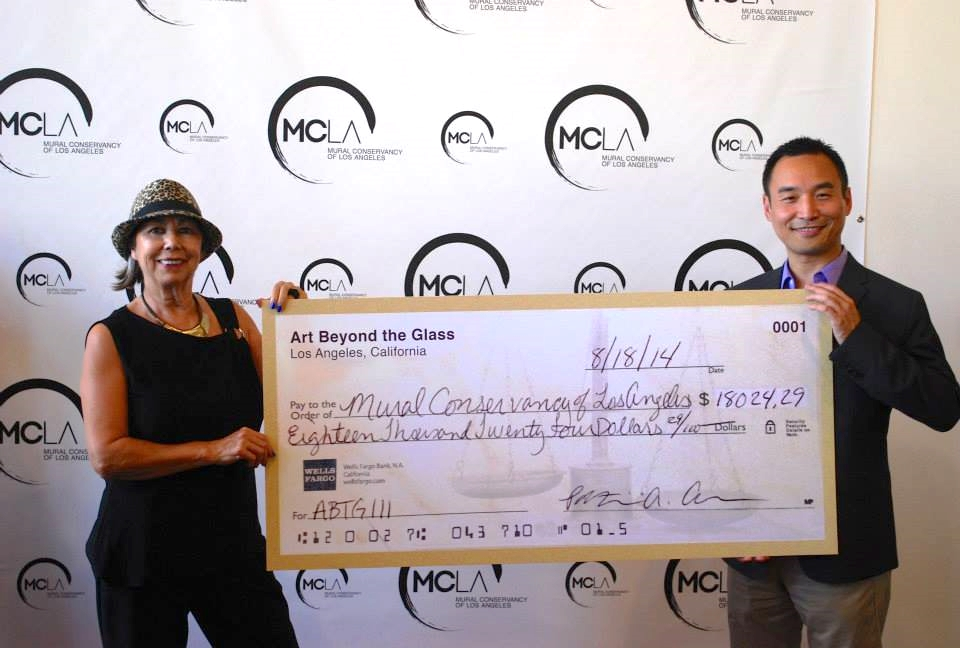 Mural Conservancy executive director, Isabel Rojas-Williams receives the Art Beyond the Glass donation check from ABTG co-founder, Daniel Djang. | Photo courtesy of Mural Conservancy, via Facebook