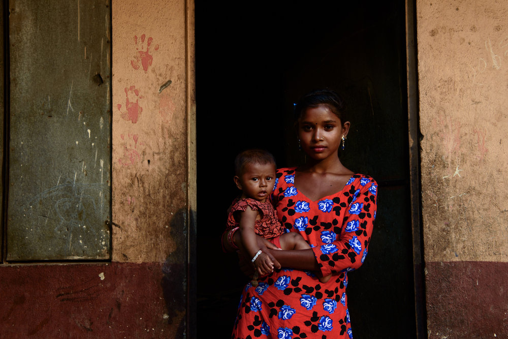 Sujita Majhi (14) holds her six month old neighbour Sumina. Sujita studied till class 5 and then dropped out of school because of her family's hard economic condition. Sujita wants to continue education but has no hope that she can do it.
