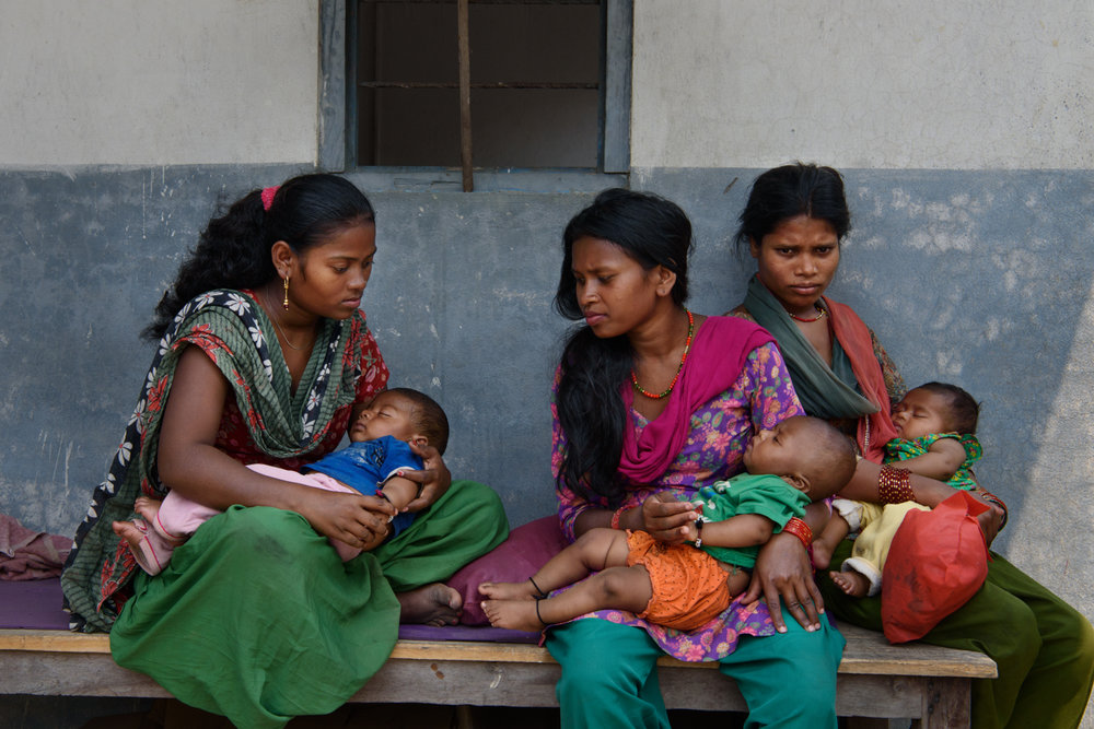 Manju Majhi (16), Tilmaya Majhi (18) and Sangeeta Majhi (19) wait for their children's treatment outside a doctor's chamber in Baghmara, Chitwan, Nepal.