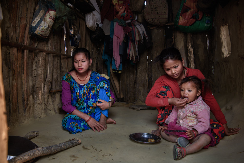 Ganga Maskimagar (17) helps her sister Kalpana Paharaimagar (19) at her home in Majhi Shivir, Chaumala, Kailali, Nepal. Both Ganga and Kalpana's husbands work in India to support their families.