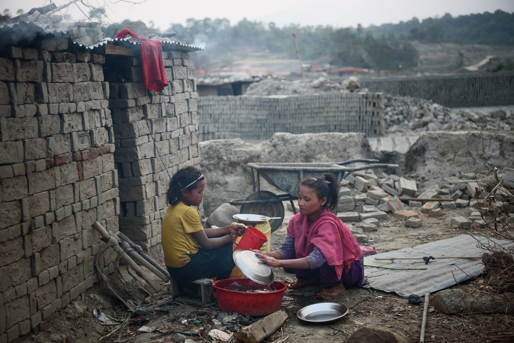 Selina Tamang (9) helps her sister Bipana Tamang (11) to wash utensils and prepare for dinner at their home in Badikhel, Lalitpur, Nepal. Bipana goes to school but Selina dropped out of school because of excessive bullying. Both the girls work in the brick kiln to assist their parents.