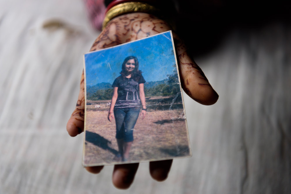 Sunita Biswakarma, 40, shows the photograph of her daughter Ranjana. Ranjana, 16, has been missing since 2009. She was trafficked by her uncle while travelling with him for a family wedding. Except for a birth certificate and a photograph, there is no other evidence of her existence.