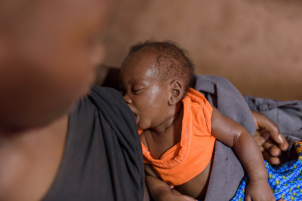 D. R., 16, with her two month old son at her home in Migori County. D. currently studies at the Ngukumahando Primary School and runs home everyday during lunch break to breastfeed her newborn.