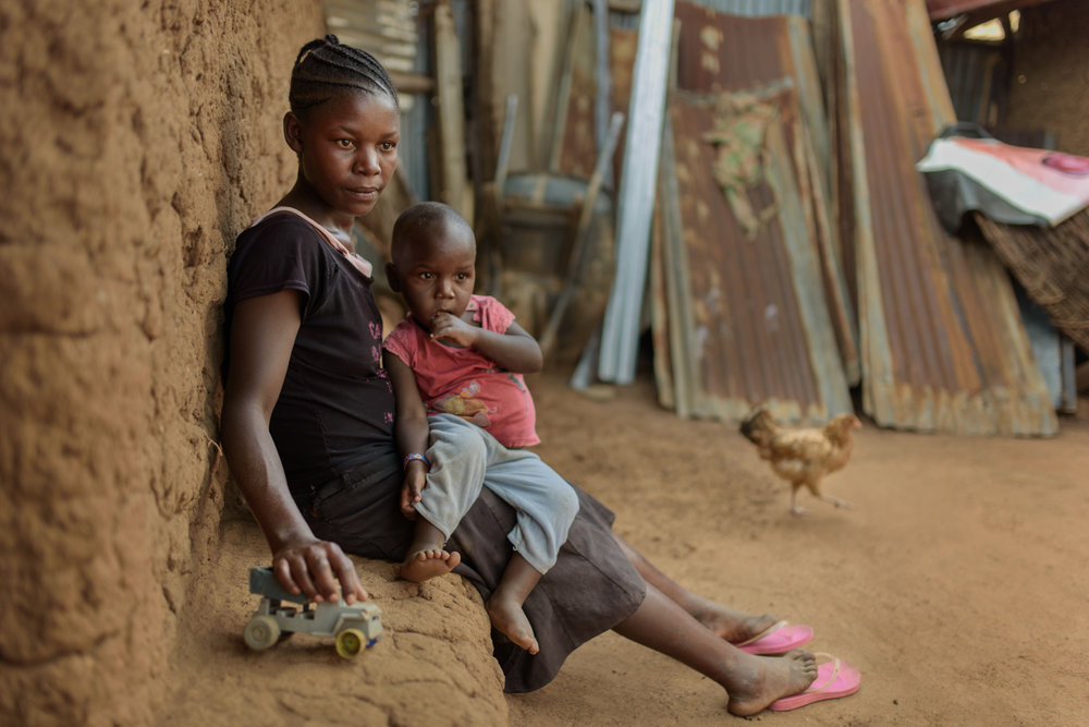 R.M., 17, with her three year old son G. at her home in Migori County. Rachel was forced by her step-brother to have sex with him. Because she feared him, she complied and ended up getting pregnant. During her pregnancy, everyone asked who the father was but she kept silent. Her family decided to report the matter to the local administration. She didn't go back to school because no one encouraged or supported her. Her sister-in-law has been supportive and asked her to help out in household chores in exchange for  money.