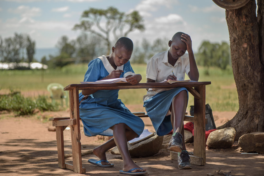 M.B., 14, (left) shares a bench with a classmate during a school examination at the Nyamotambo Primary School, Migori County. Mary is pregnant and an orphan who lives with two younger siblings. Her two older brothers who work in Nairobi send her money for her living expenses.