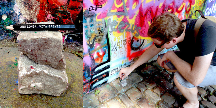 Dropping a pencil at the John Lennon Wall in Prague, Czech Republic.