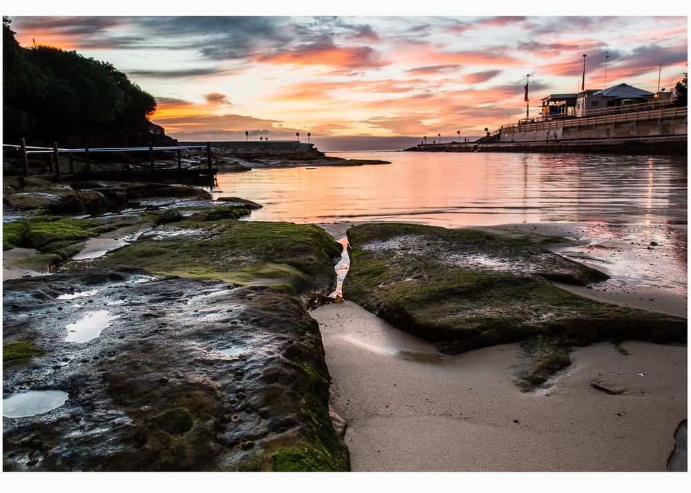 This is my favourite - dramatic sky; tranquil water. rocks and the iconic surf club.
