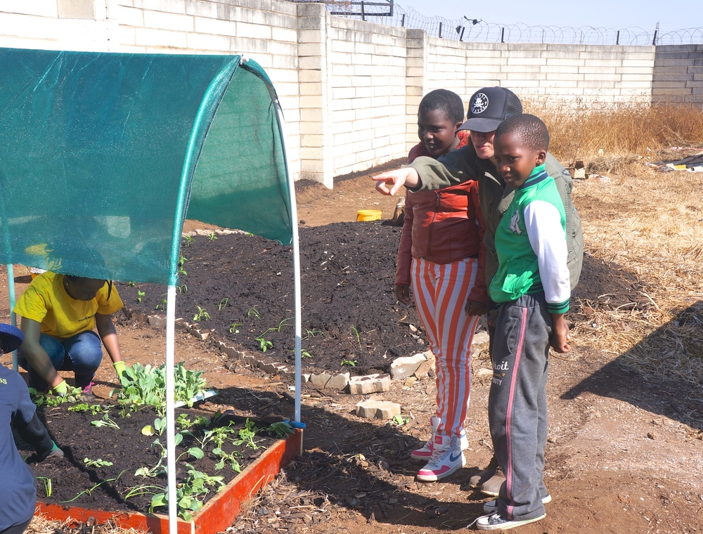 Recruiting some young gardeners from Tladi to help plant our first batch of seedlings.