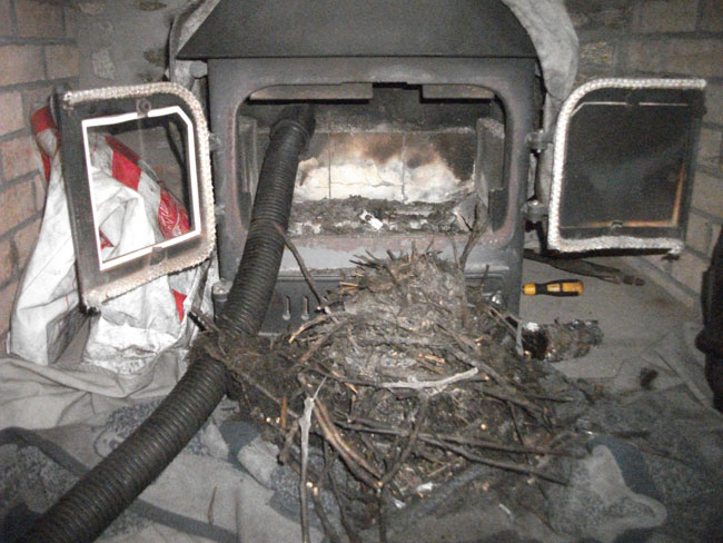This is a birds nest blockage above a wood burner.  Our power sweeping service allows us to remove all the debris and soot.
