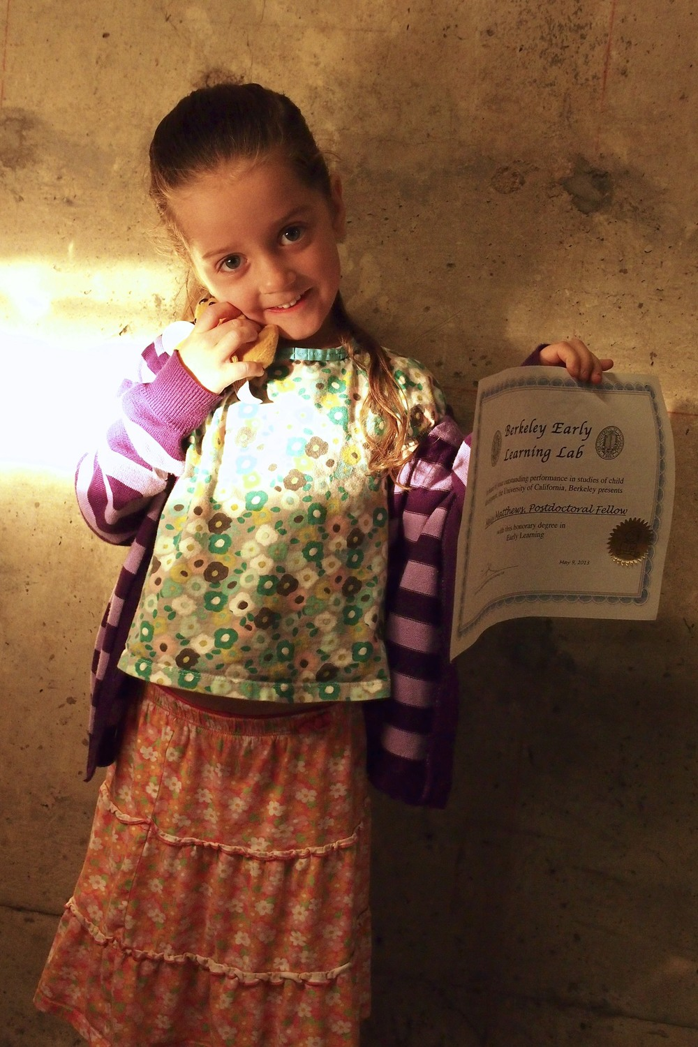 Maisy shows off her doggy toy and her diploma in the parking garage as her sister flashes the high beams from the driver's seat of our car.