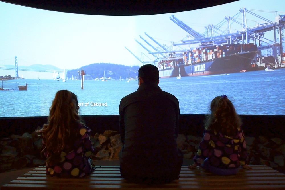 Todd and the girls watching a film about the ports of the Bay.