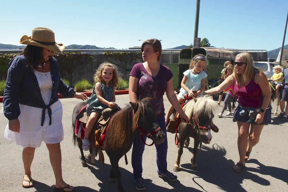 Maren and Maisy riding their ponies with their special mommy friends next to the bay.