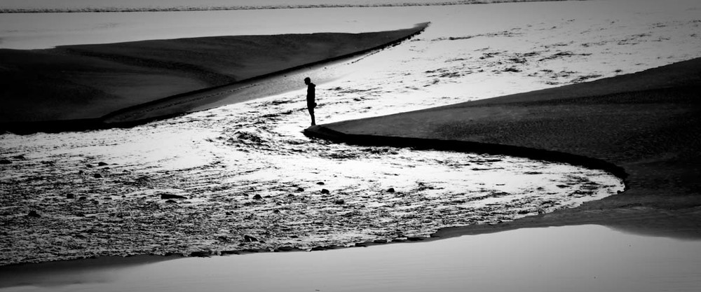 A man solemnly stares into water desperately wandering its way to the ocean. Oregon Coast.