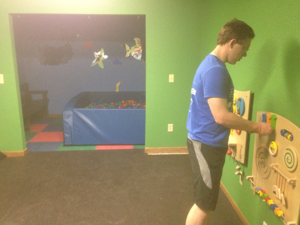 The repainted sensory room with new Paint, soft flooring, trim, wall decorations, and wall puzzles.