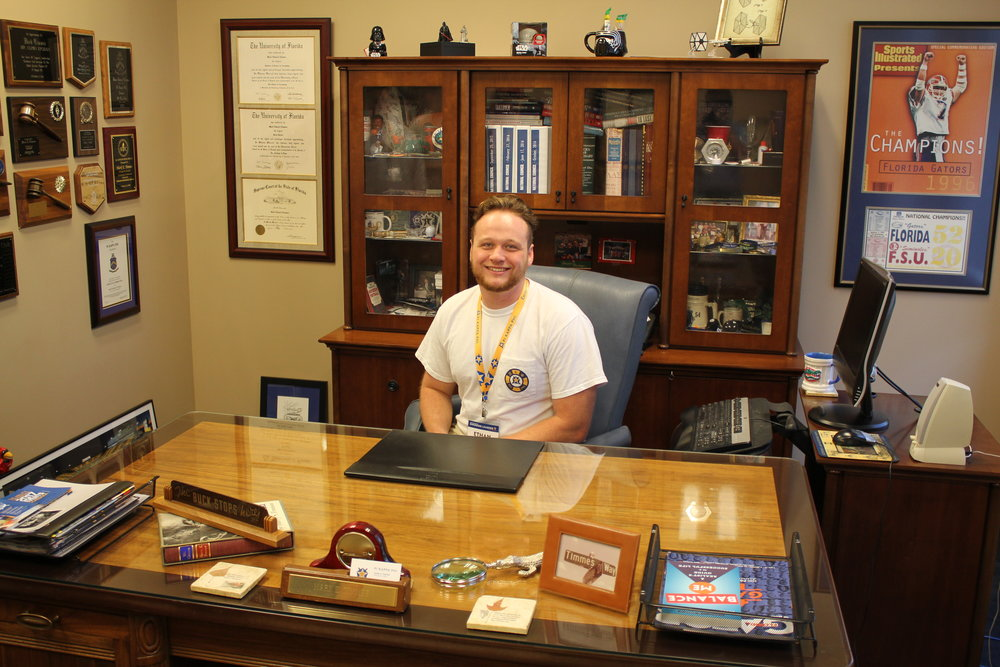Ethan Ennis sitting Mark E Timmes' desk. Timmes is the CEO of our national organization.