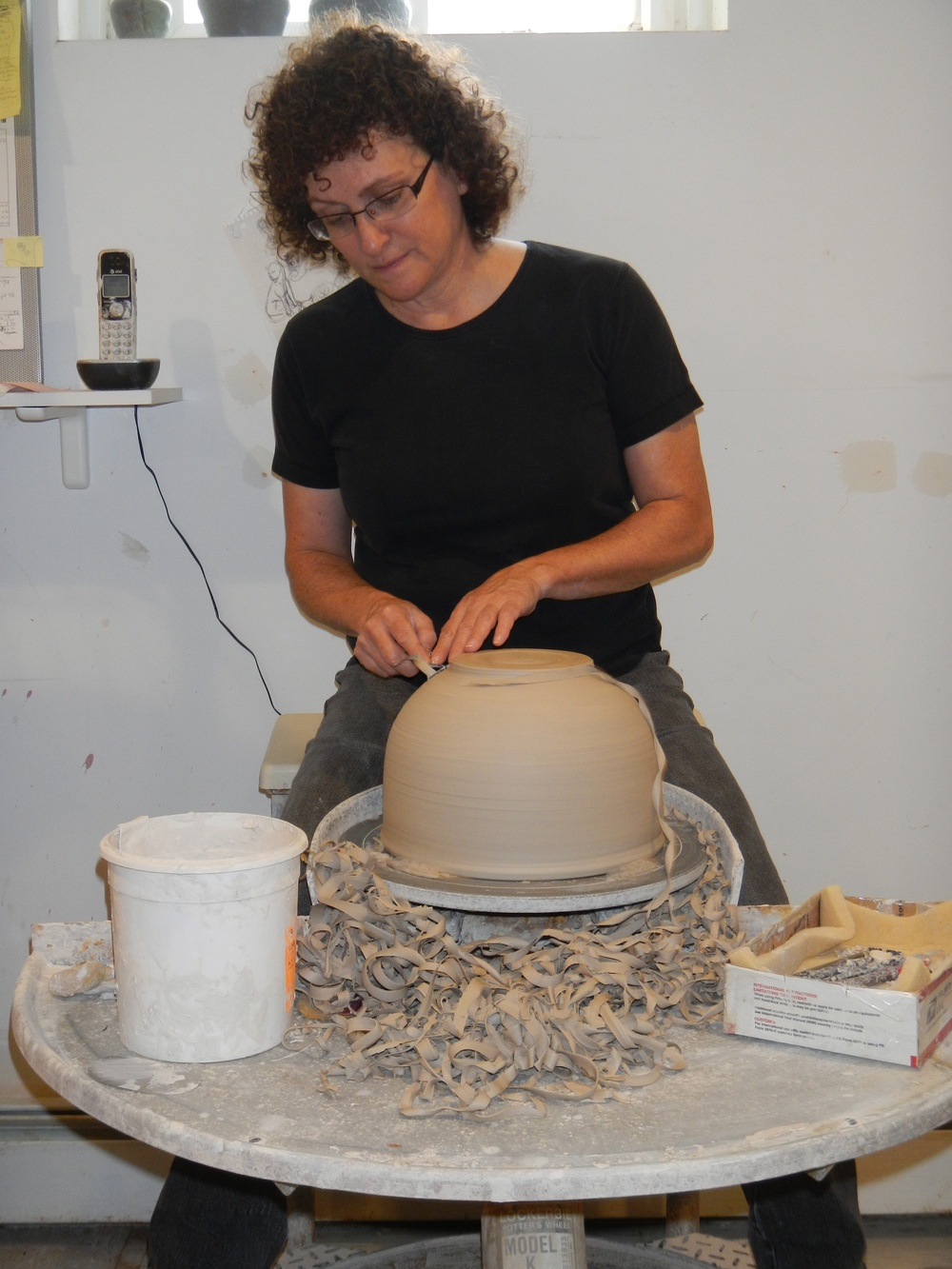 (Trimming a bowl at my trusty kickwheel. Photo Madelene Hoffman 2012)