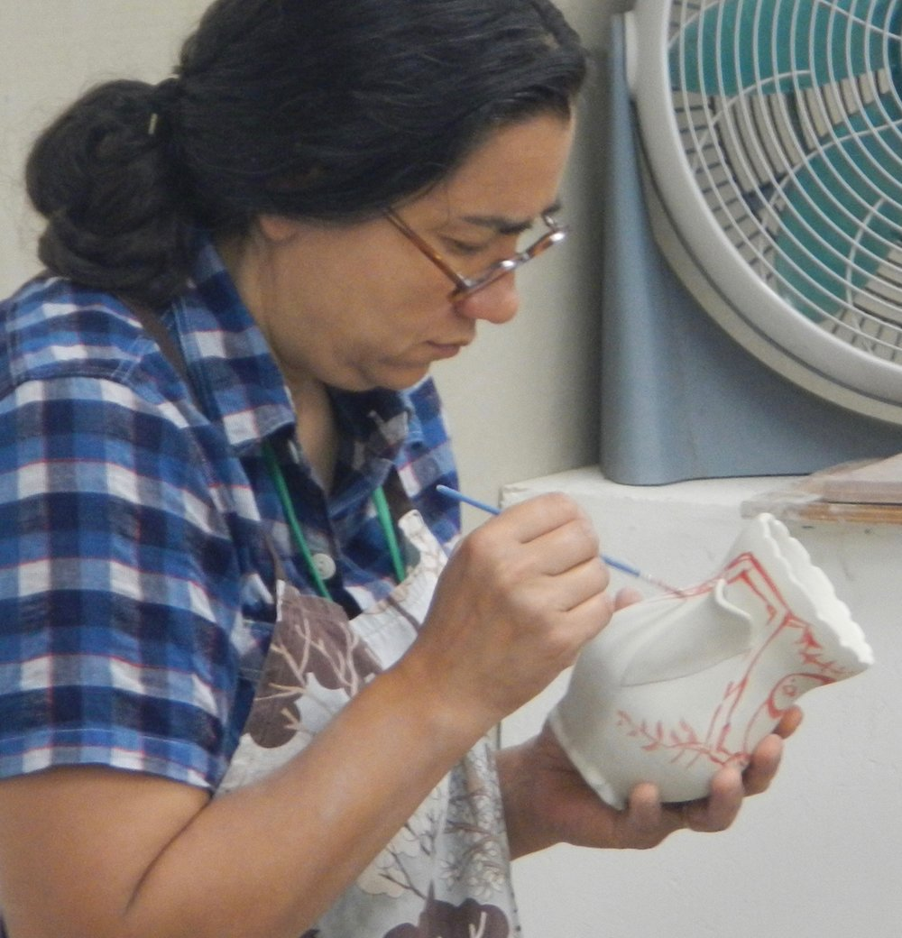 (Ayumi applying luster (like the lustered bird in the previous photo) over a glaze-fired white pot)