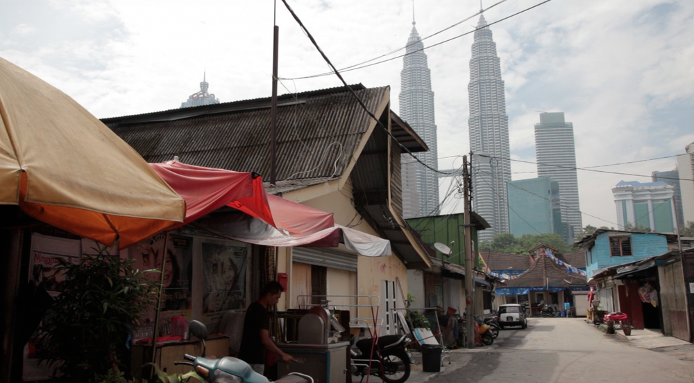 The Petronas Towers rise above a Kuala Lumpur street.