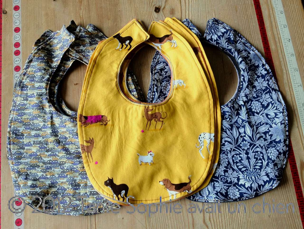 …  baby bibs  … the ones from the purlbee … using up some fabric stash … i back them with old t-shirts … quite alright and quickly done … must sew on the big snaps … liberty of london tana lawn in the car print and the beautiful william morris style flower print in blue and white … the dogs on yellow are an old  heather ross  fabric … happy bibs all around …