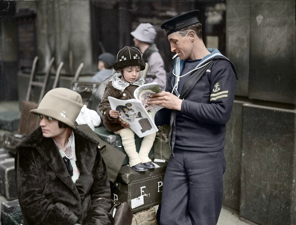 A sailor reads with his child while he waits for a holiday train at Waterloo Station in London, 1927. Colorized by  crumbleater