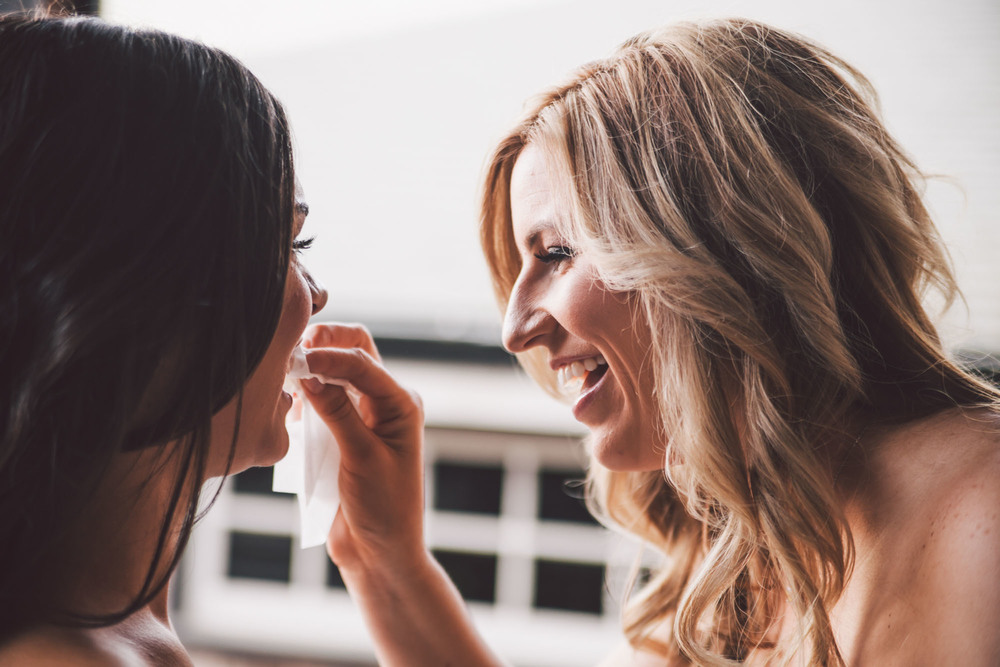 bridesmaid fixing bride's makeup