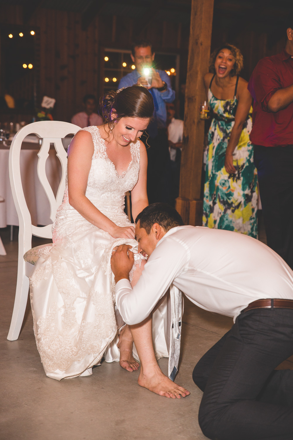 groom removing garter with his teeth