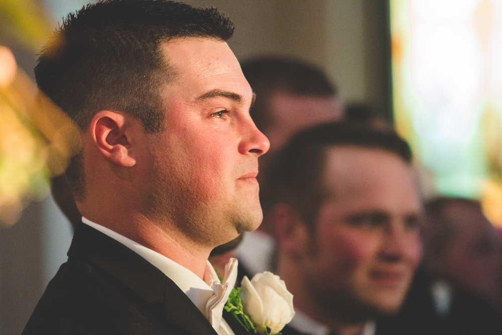 groom crying while bride walks up aisle