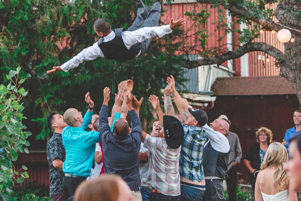 guests tossing groom in air