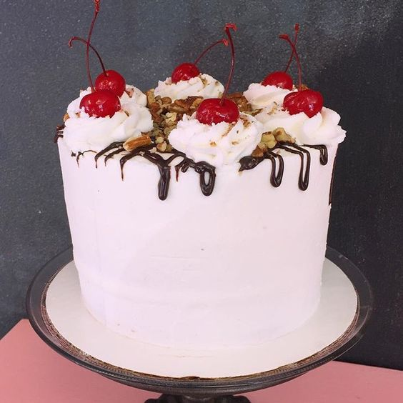 Split Personality - 3 layers of White Velvet Cake filled with fresh pineapple, strawberry and banana. Frosted with Buttercream. Topped with ganache pecans and cherries.   6 inch $35 8 inch $45