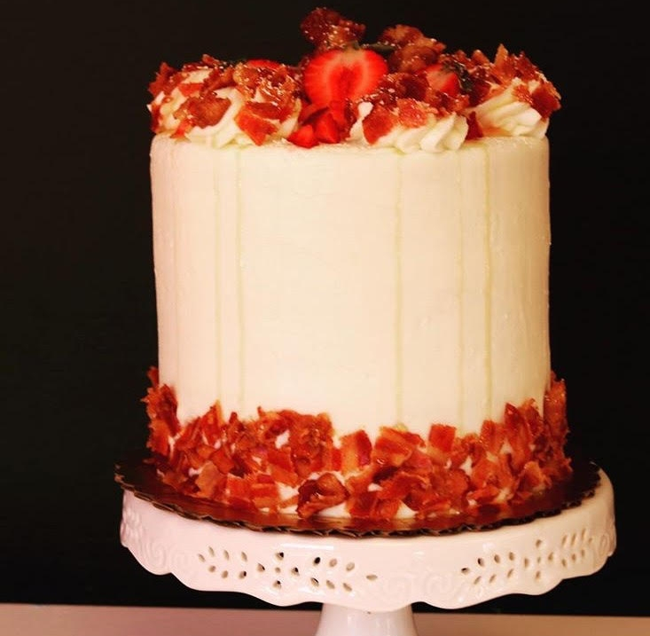 French Toast - 3 layers of Muffin cake soaked with maple syrup. Frosted with Cream Cheese Buttercream drizzled with maple syrup and decorated with bacon crumbles and fresh fruit.   6 inch $35 8 inch $45