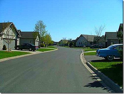 Typical suburban street with an uninviting streetscape and unsafe street width.