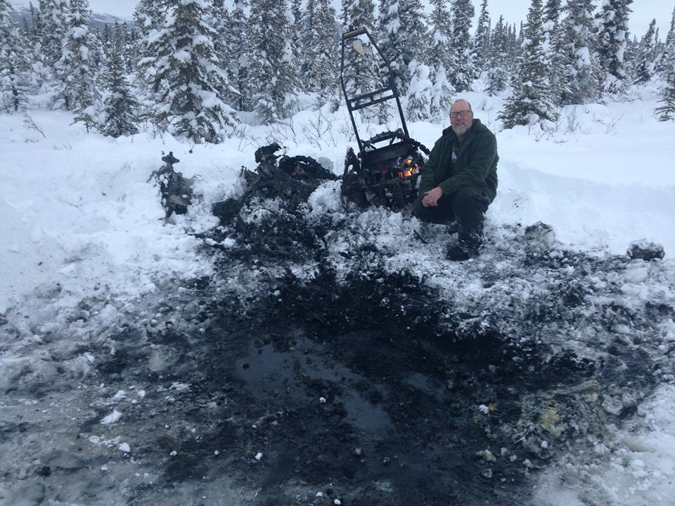 Claude with his snowmachine after it burst into flames.