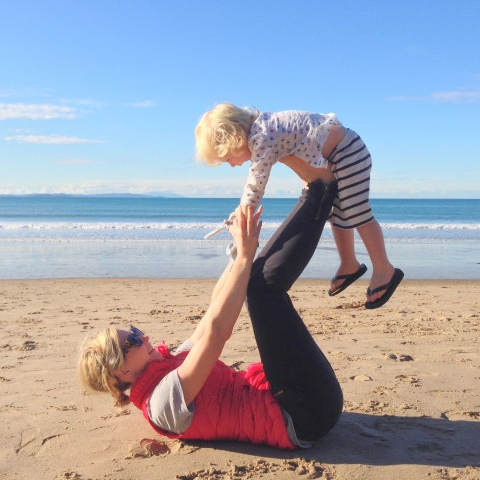 Rachel Grunwell doing yoga with her son Takapuna beach