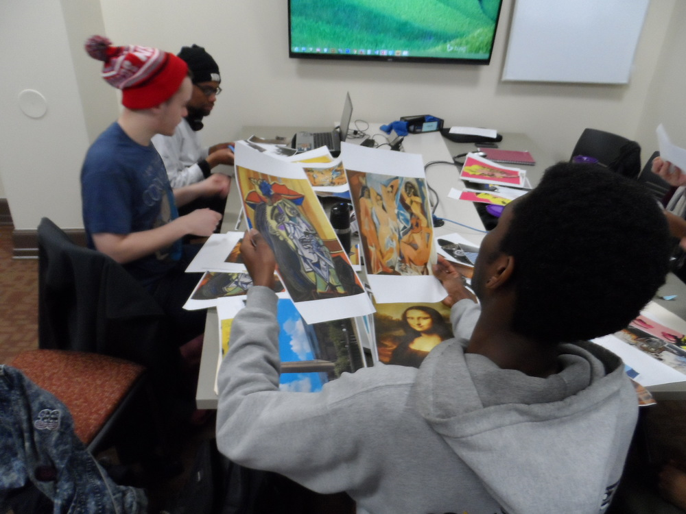"This student compares two works from Picasso, ""The Crying Woman"" in the left hand  and ""Les Demoiselle d'Avignon"" in the right hand as Leonardo da Vinci's Mona Lisa lay on the table adjacent to an image of the Tate Modern in London. All referenced in Jay Z's song ""Picasso Baby""."