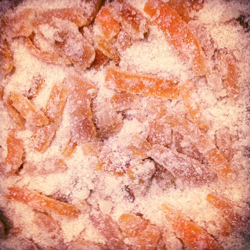 Once peels became translucent, my son scooped them out onto a tray of sugar. We tossed them around to get full sugary coverage, and now they sit and wait to be eaten...