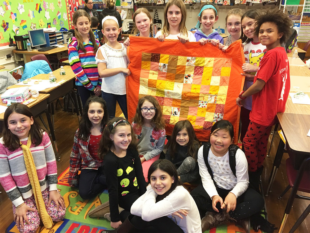 Future generation of quilters showing off their first finished piece.