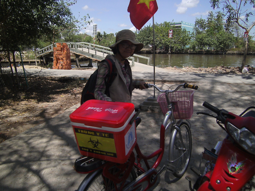 Yen carrying an esky full of samples on the back of her bicycle during village screening