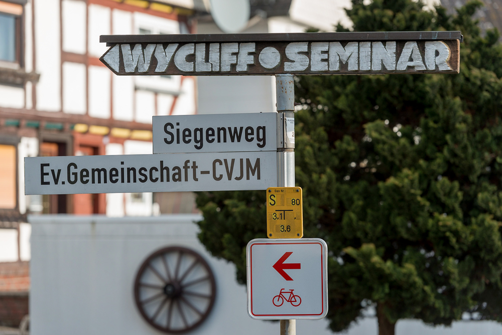 On top of a municipal street sign post, a wooden, hand-painted directional sign indicates the location of the Wycliffe Germany's offices in Holzhausen, Germany.